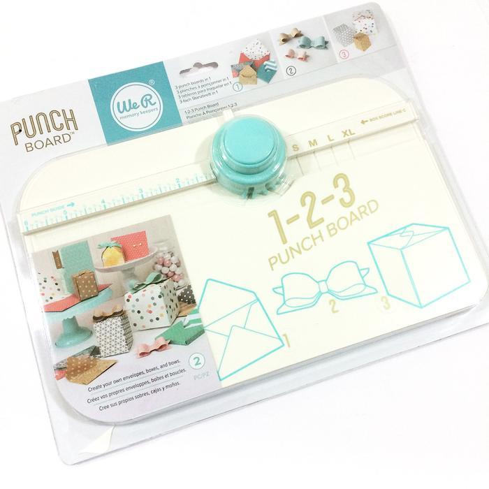 We R Memory Keepers-123 Punch Board. Crea sobres, cajas y lazos. El tablero cuenta con un brazo desplegable con medidas y una línea de puntaje extendida. Este paquete de 9-1 / 2x12x2 pulgadas contiene un marcador con un punzón de 3 vías, una herramienta de puntuación y un libro de ideas con instrucciones paso a paso.