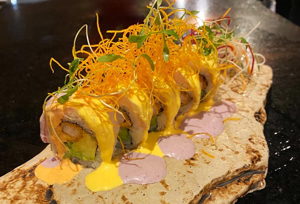 Relleno de salmón, kiuri y palta, cubierto de shiromi con salsa de ají amarillo, rocoto y aceituna.