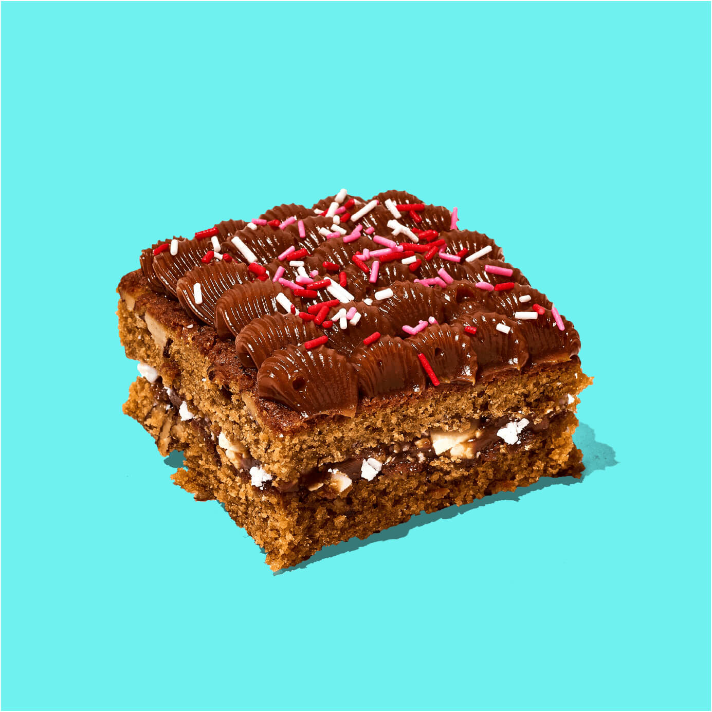 Delicioso Brownie blondie relleno de manjar con trozos de chocolate blanco. Decorado con manjar blanco y confites.  Medida de Producto: 6.5 cm de ancho, 6.5 cm de largo, 3.5 cm de altura