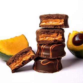 Delicioso mini alfajor relleno de una crema a base de pulpa de lúcumacon cobertura de chocolate y líneas de glasé color anaranjado.