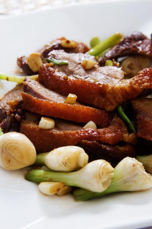 Pato salteado con cebolla china y trozos de ajos que realzan su sabor.