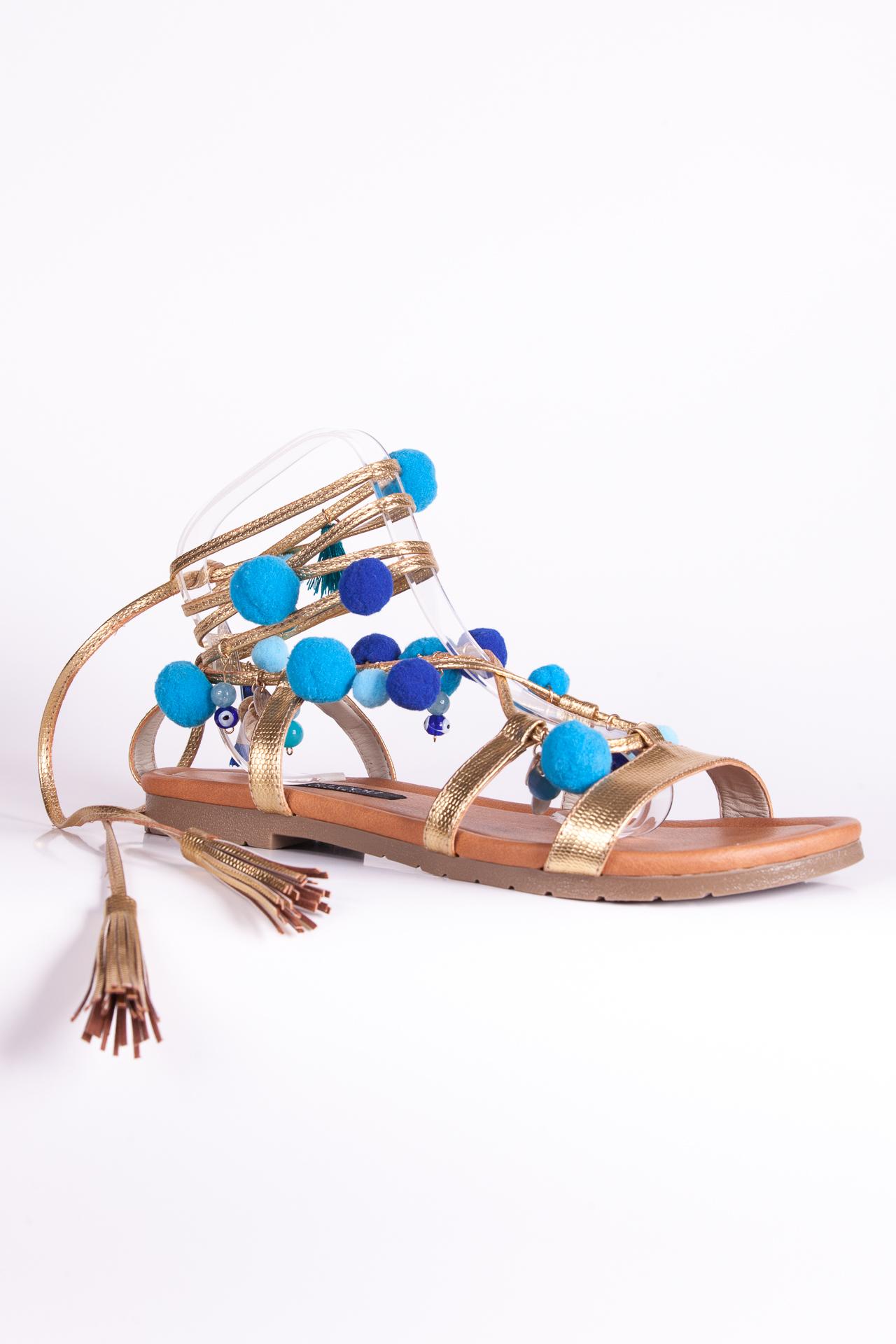 Sandalias doradas con pompones y aplicaciones. Confeccionadasa mano.