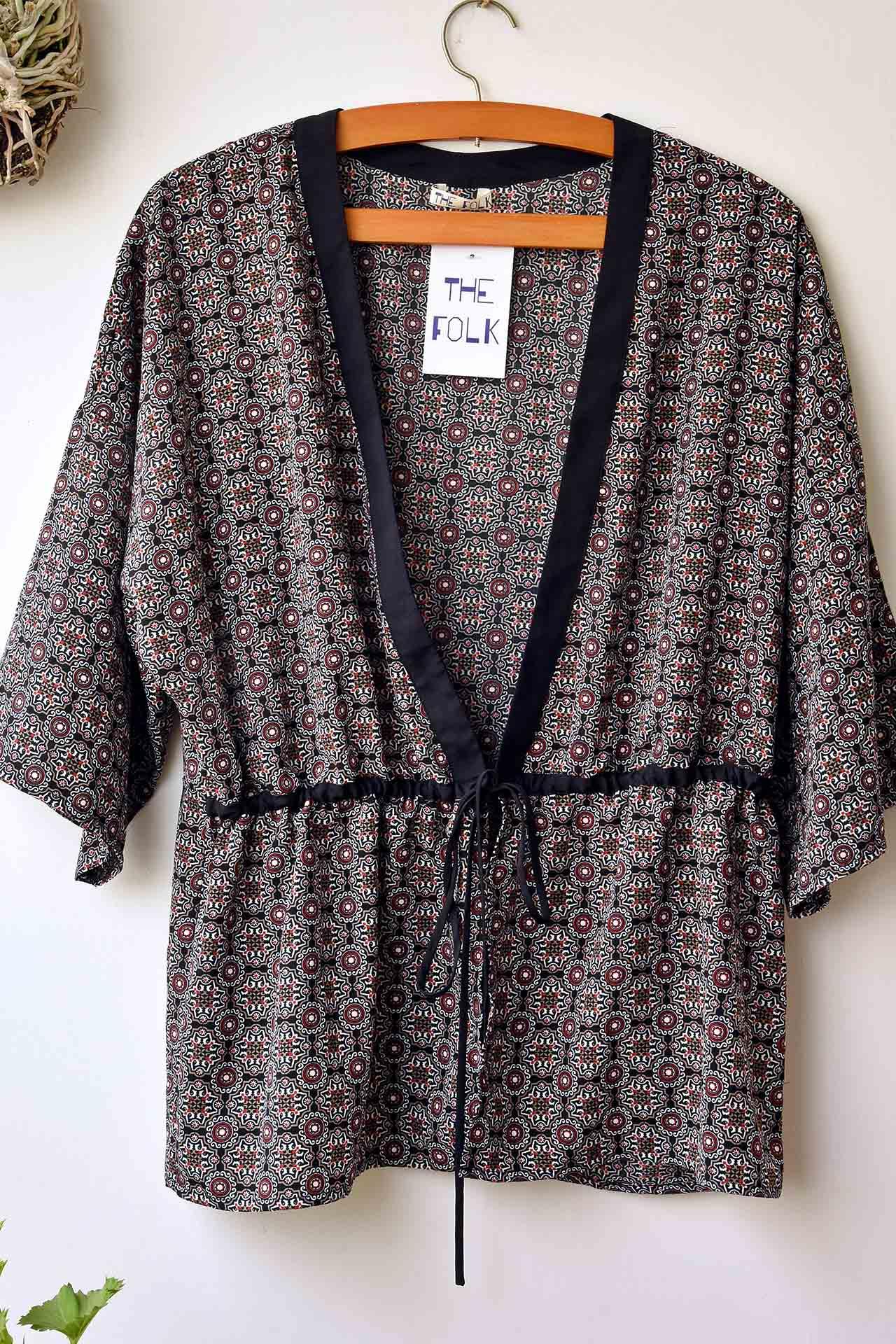 Kimono fondo negro con print en blanco y rojo. La tela es super suave y tiene una cintita para que te amarres el kimono a la altura de la cintura.