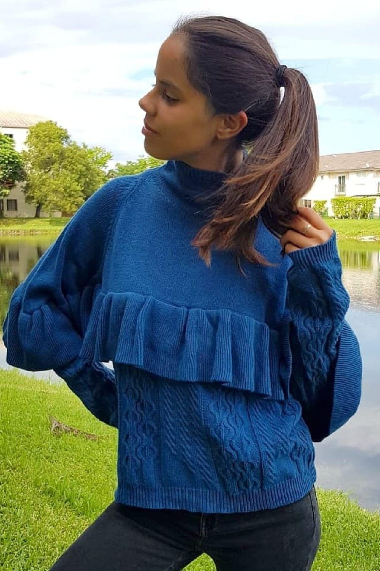 Chompa de lana con cuello alto con bobos en el pecho.