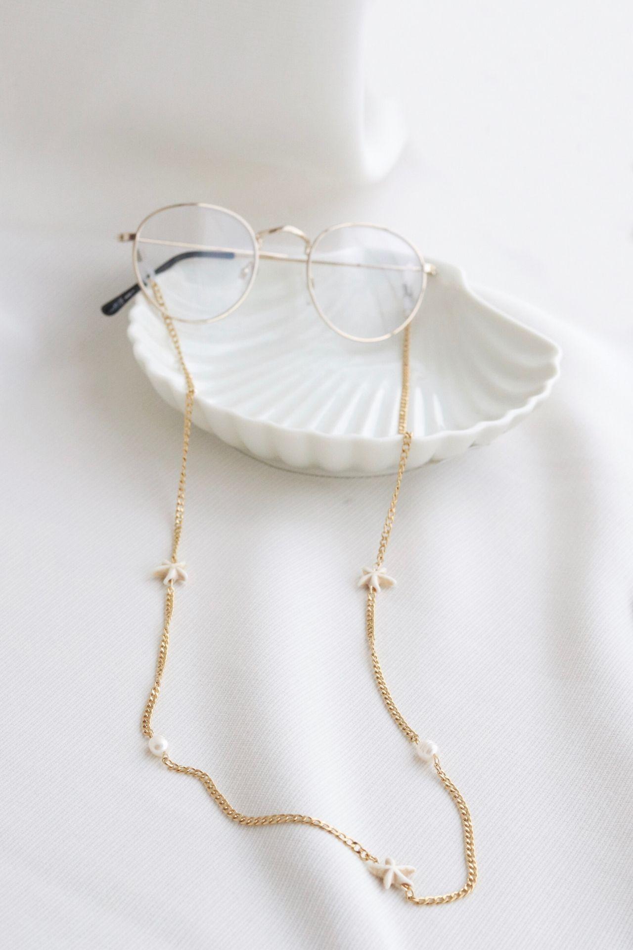 Holder de lentes con detalles de estrellas y perlas.  Material: acero.