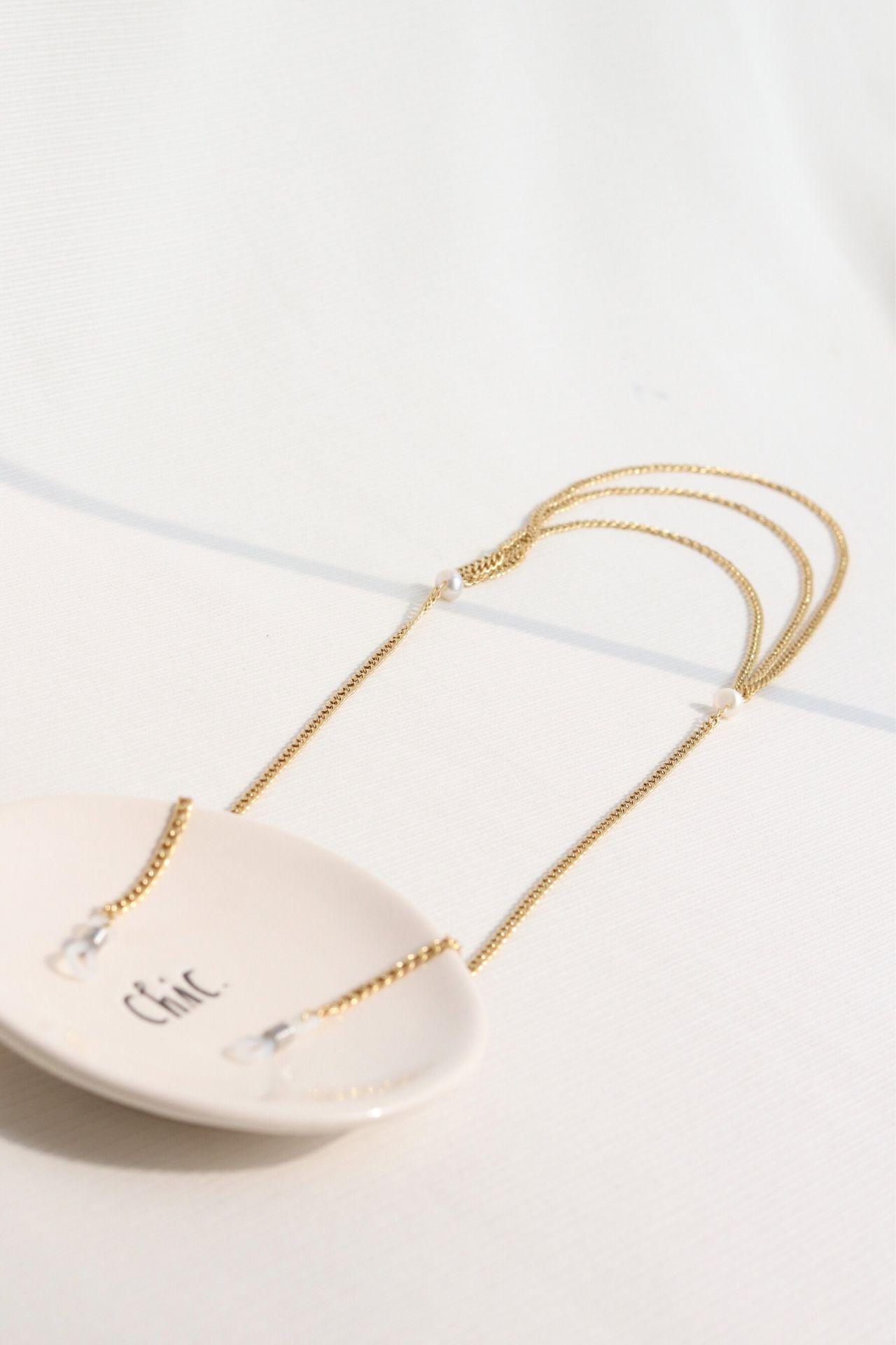 Holder de lentes de acero con perlas de río.