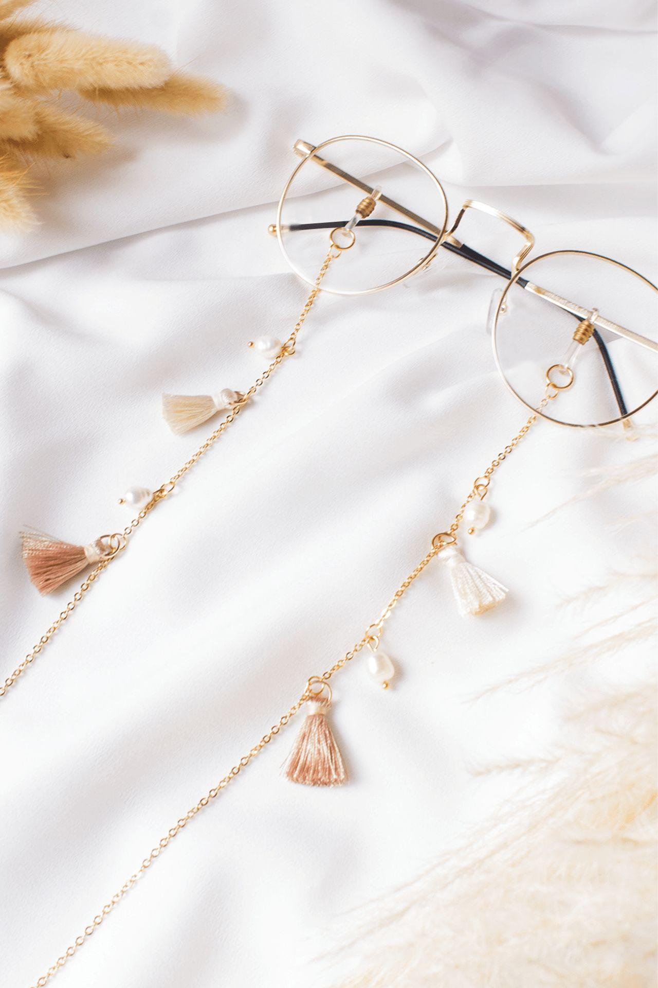 Descripción: Sujetador de lentes con perlas de río y pompones.  Material: Acero