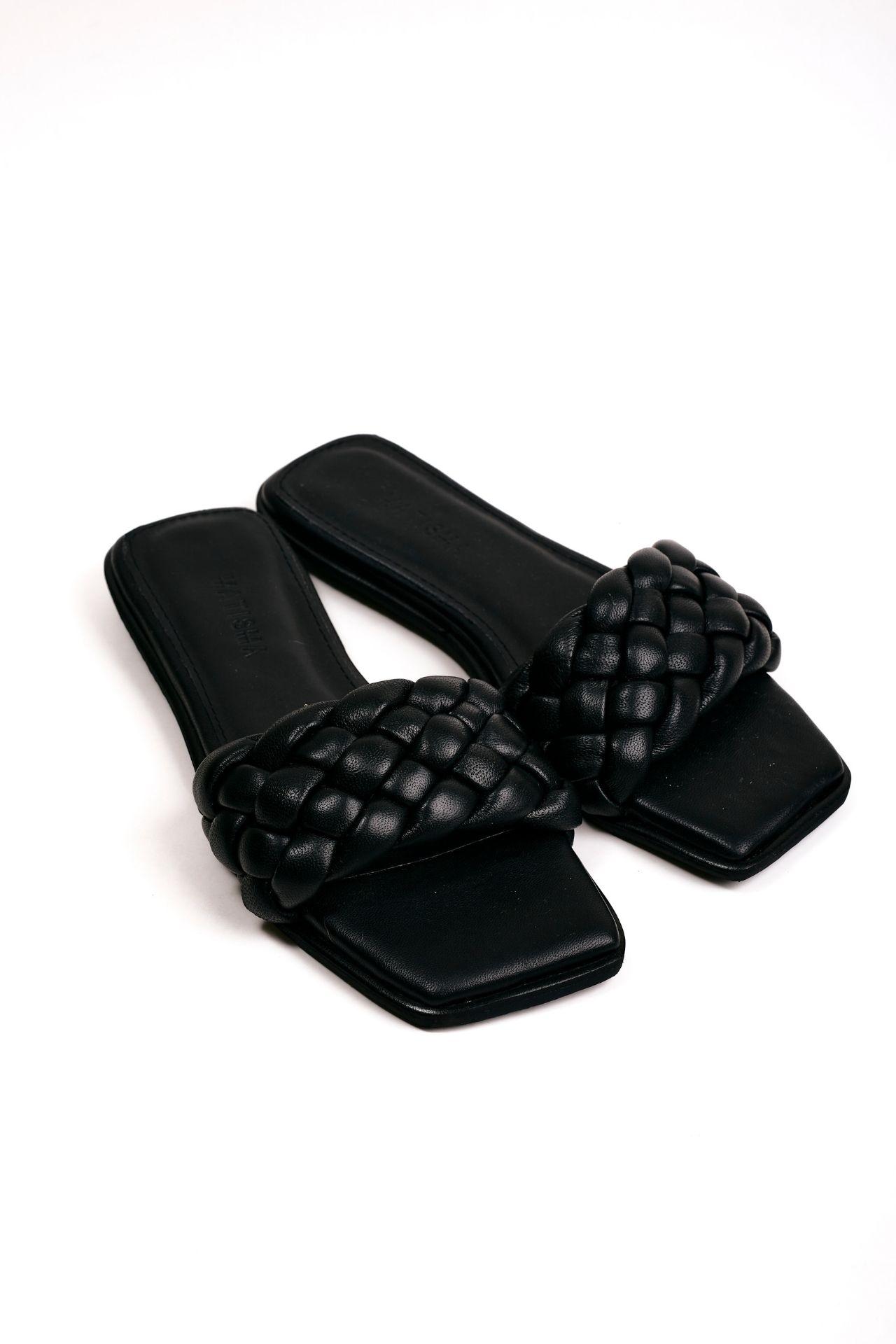 Sandalias con una franja trenzada de cuero negro.  Capellada: Cuero natural  Forro: Badana Natural