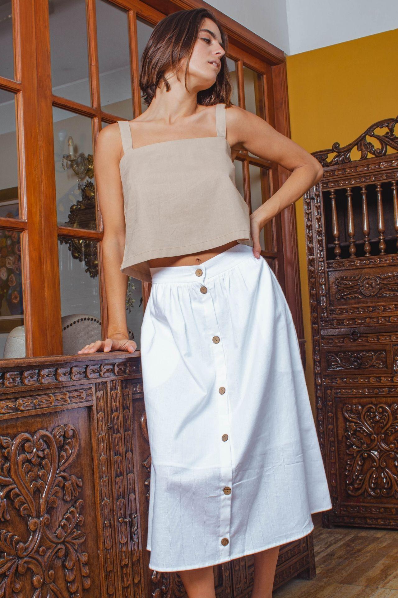 Falda midi a la cintura con bolsillos laterales y botones en el centro de la falda. Tela lino. Cuenta con forro para que no trasluzca. Los botones son funcionales.  Medidas:  S: cintura (68 cm) largo (72 cm)  M: cintura (72 cm) largo (72 cm)